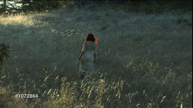 WS Woman in white dress walking up sunlit hill/ Marin County, California