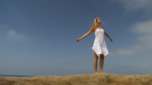 woman in white dress walks and dances on sand berm at the beach - サンドレス点の映像素材/bロール