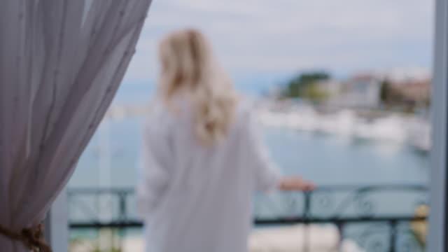vidéos et rushes de femme de ws dans la chemise blanche appréciant un air frais sur le balcon par la mer - croatie