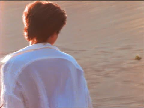 woman in white shirt on beach walking away from camera / turns + walks toward camera / smiles - white shirt stock videos & royalty-free footage