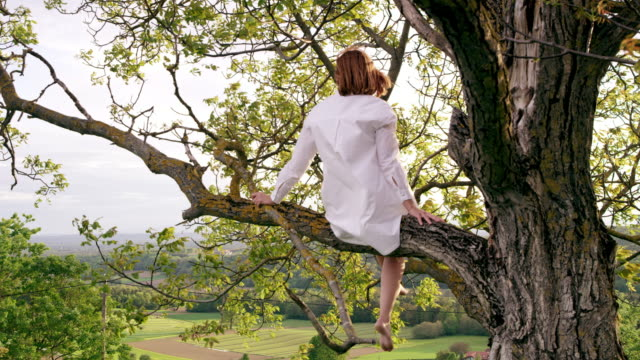 slo mo woman in white shirt sitting on a tree - all shirts stock videos and b-roll footage
