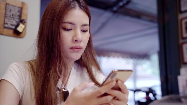 ダウンタウンの近くのカフェを検索するための携帯電話アプリケーションを使用して白いシャツを着た女性、 - 記事点の映像素材/bロール