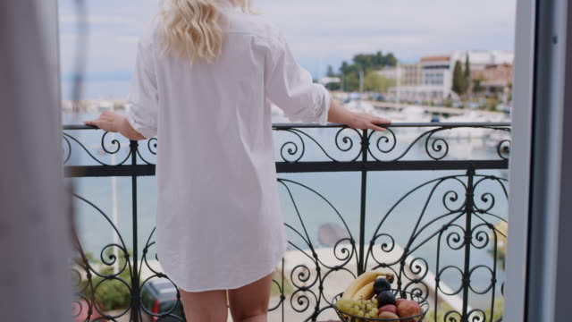 ws woman in white shirt walks on the balcony by the sea - vista marina stock videos & royalty-free footage