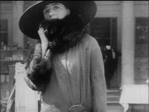 b/w 1917 woman in wide-brimmed hat + fur-trimmed coat looking at camera - 毛皮のコート点の映像素材/bロール