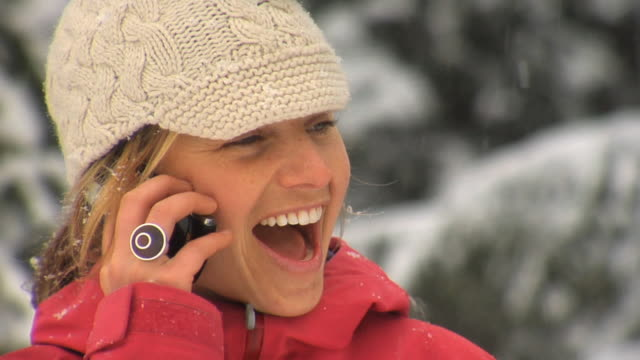 SLO MO CU Woman in winter clothes talking on cell phone, Whistler, British Columbia, Canada