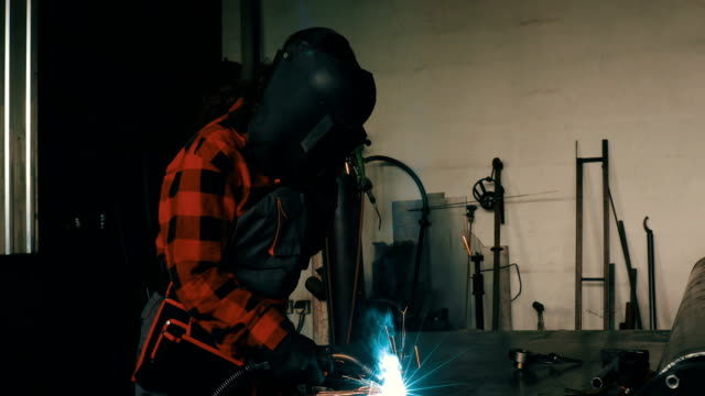Woman in workshop welding 4K