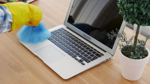 Frau im gelben Handschuhe mit blauen Bürste für die Reinigung des Staub auf laptop