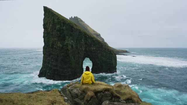 woman in yellow raincoat looking at drangarnir arch in faroe islands - distant stock videos & royalty-free footage