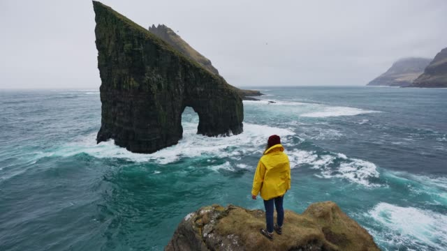 woman in yellow raincoat looking at drangarnir arch in faroe islands - cliff stock videos & royalty-free footage