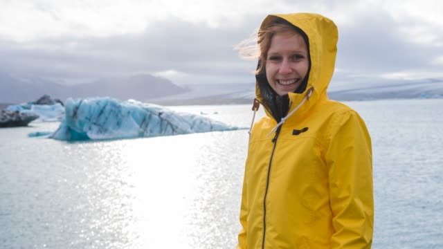 woman in yellow raincoat looking at icebergs - hood clothing stock videos & royalty-free footage