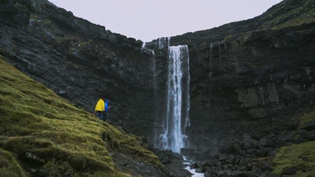 vidéos et rushes de femme dans le imperméable jaune restant près de la chute d'eau dans les îles féroé - vue de face