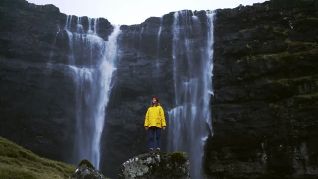 woman in yellow raincoat standing near the waterfall in faroe islands - contrasts stock videos & royalty-free footage