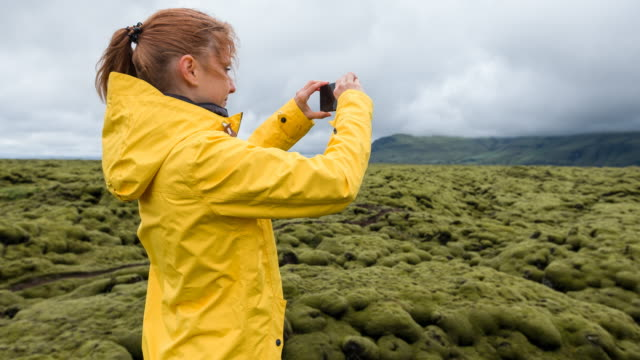 woman in yellow raincoat taking pictures of green and mossy volcanic landscape on a windy day - mgost stock videos and b-roll footage