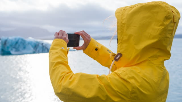 woman in yellow raincoat taking pictures of icebergs in jokulsarlon glacial lake - hood clothing stock videos and b-roll footage