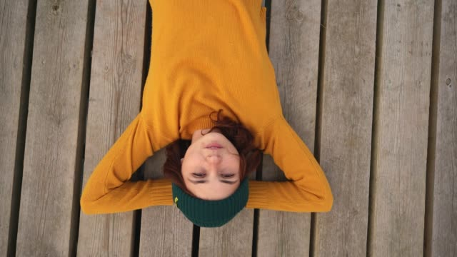 woman in yellow sweater laying on pier and looking up - top capo di vestiario video stock e b–roll