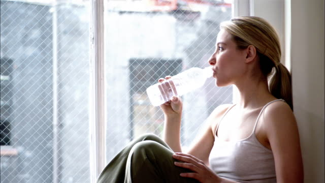 vidéos et rushes de woman in yoga clothing sitting in windowsill and holding bottle of water laughing and talking to camera / drinking water - bouteille d'eau minérale