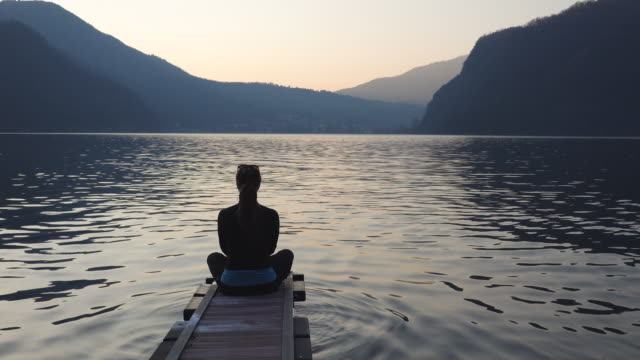 woman in yoga pose at the end of dock on lake meditating - the way forward stock videos & royalty-free footage