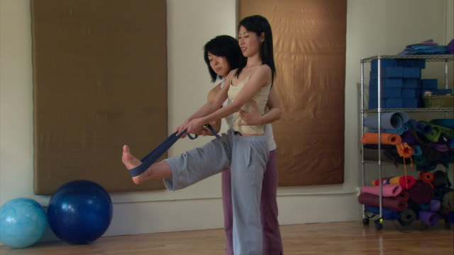 MS ZI Woman in yoga studio holding right leg up with a strap as instructor holds her up/ New York, NY