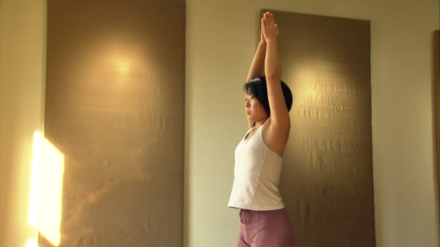 ms tu woman in yoga studio stretching and bending over/ new york, ny - bending over stock videos & royalty-free footage