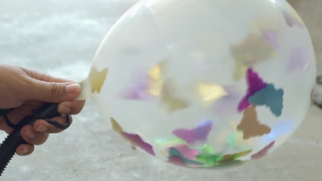 woman inflates a balloon with colored paper inside - balloon stock videos & royalty-free footage