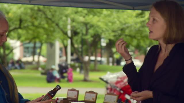 ms pan woman inquires about bottle to woman / burlington, vermont, usa  - burlington vermont stock videos & royalty-free footage