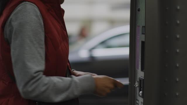 vídeos de stock e filmes b-roll de woman inserting a card into a machine - parking