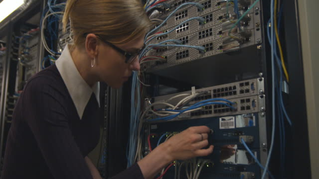 CU Woman inserting cables into back of computer server, Sydney, Australia