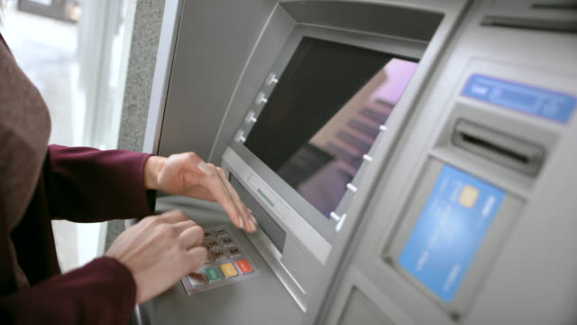 ld woman inserting her bank card and shielding the keypad while entering pin - money stock videos & royalty-free footage