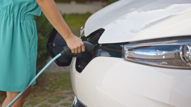 slo mo woman inserting plug into electric car - electrical plug stock videos & royalty-free footage