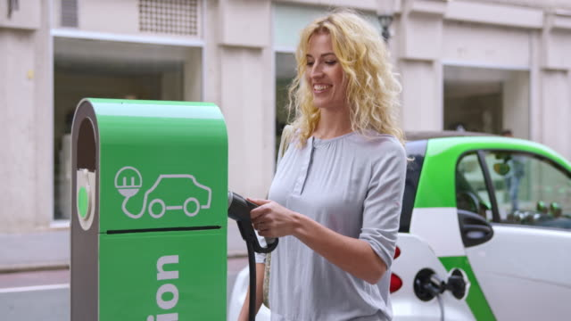SLO MO Woman inserting plug into EV station