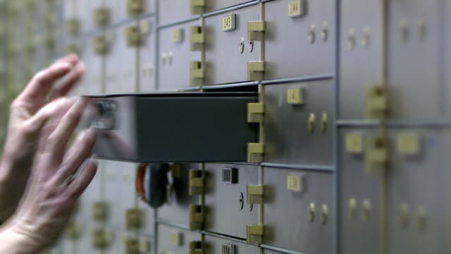 cu selective focus woman inserting safe-deposit box, bethlehem, pennsylvania, usa - 銀行点の映像素材/bロール