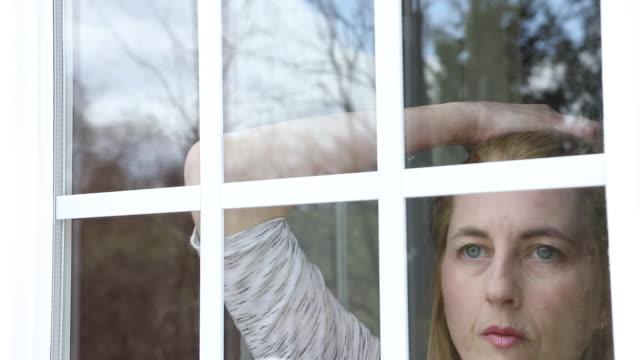 woman inside looking through window - blonde hair stock videos & royalty-free footage