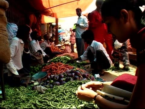Woman inspecting pea pod at outdoor vegetable market / Bangalore, Karnataka, India