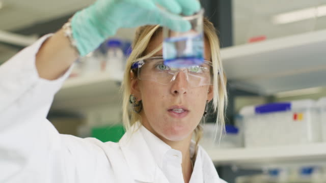 ms a woman inspects a sample in a genetics laboratory - becher video stock e b–roll