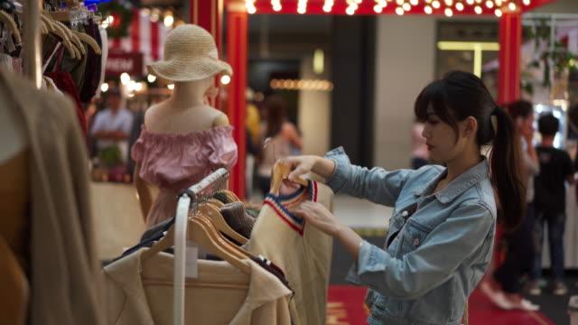 vídeos de stock, filmes e b-roll de woman inspects clothes in mall, close up - jaqueta jeans