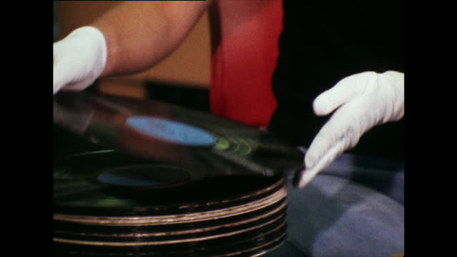 vídeos de stock, filmes e b-roll de woman inspects vinyl records before packing; 1973 - 1973