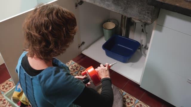 woman installing a plumber's snake to a cordless drill - waschbecken stock-videos und b-roll-filmmaterial