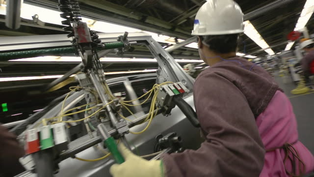 stockvideo's en b-roll-footage met ms pan woman installing side door on minivan in an auto assembly plant / princeton, indiana, united states - autofabriek