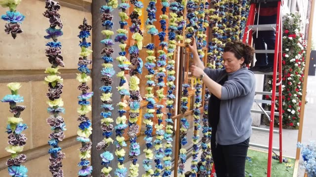 A woman installs a floral window display at the Bulgari store near Sloane Square as businesses unveil this years creations in support of the Chelsea...