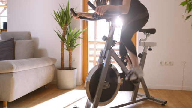 slo mo woman intense cycling on the exercise bike - exercise machine stock videos & royalty-free footage
