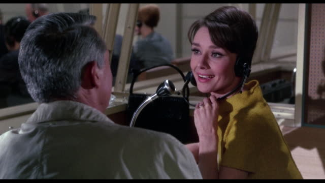 1963 woman (audrey hepburn) interrupts translation job to follow up lead with amorous man (cary grant) - 言語翻訳点の映像素材/bロール