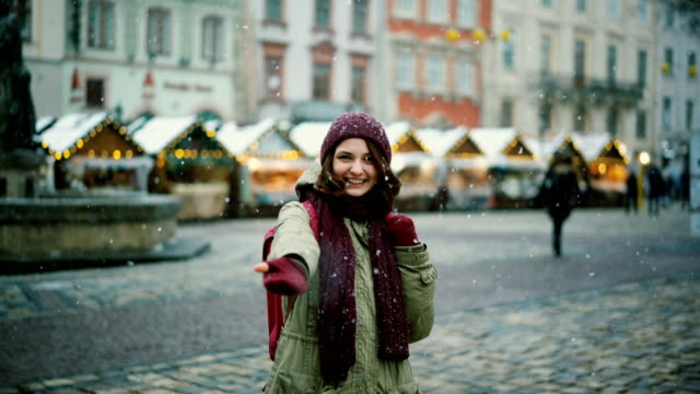Woman inviting to walk on Christmas market
