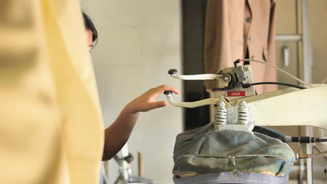 ms woman ironing shirts in dry cleaners / richmond, virginia, usa. - iron appliance stock videos and b-roll footage