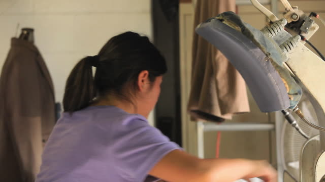 ms woman ironing shirts in dry cleaners / richmond, virginia, usa. - bügelbrett stock-videos und b-roll-filmmaterial