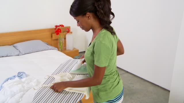 vídeos de stock e filmes b-roll de woman ironing - fotografia de três quartos