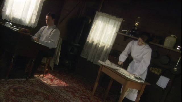 a woman irons as her husband sits at a writing desk. - 19th century stock videos & royalty-free footage