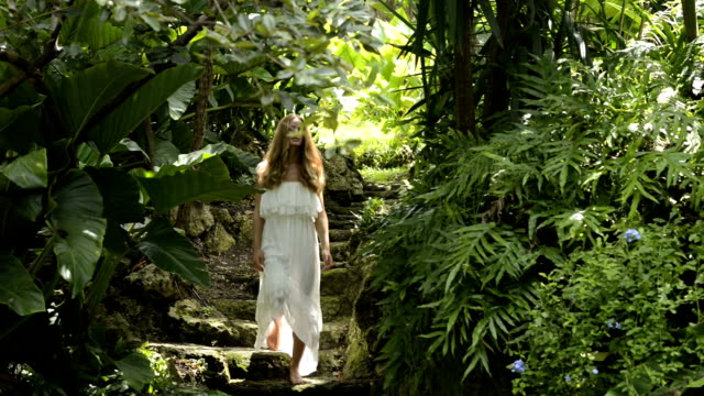 stockvideo's en b-roll-footage met woman is arriving in a tropical pool - formal garden