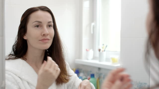 woman is brushing hair after shower with hair brush in bathroom shot on red epic - verlust stock-videos und b-roll-filmmaterial