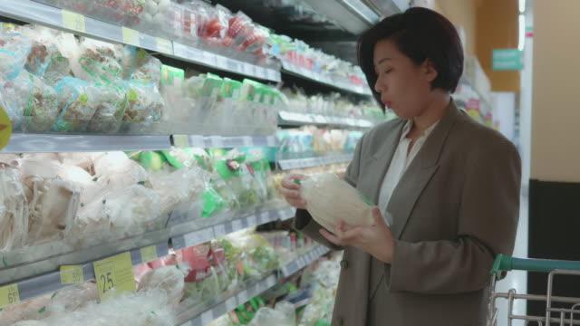 ある女性がスーパーで野菜を買っている。 - 買い物袋点の映像素材/bロール