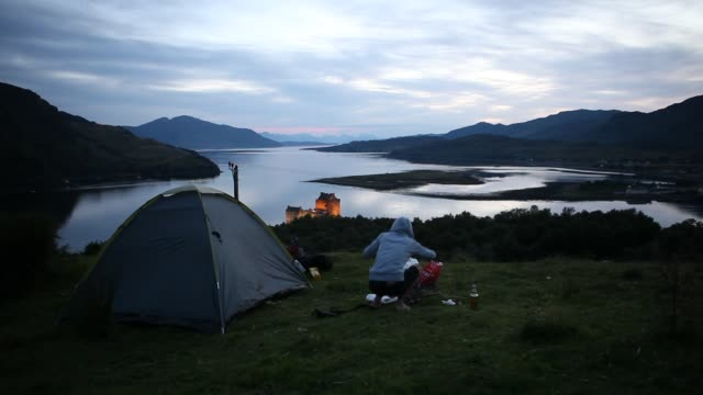 a woman is camping with her tent next to the eilean donan castle on an island in loch duich is only accessible via a stone bridge - see loch duich stock-videos und b-roll-filmmaterial